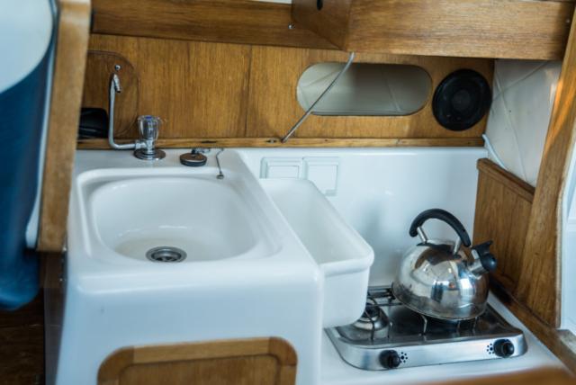 Kuchnia gazowa i zlew w kambuzie łodzi motorowej